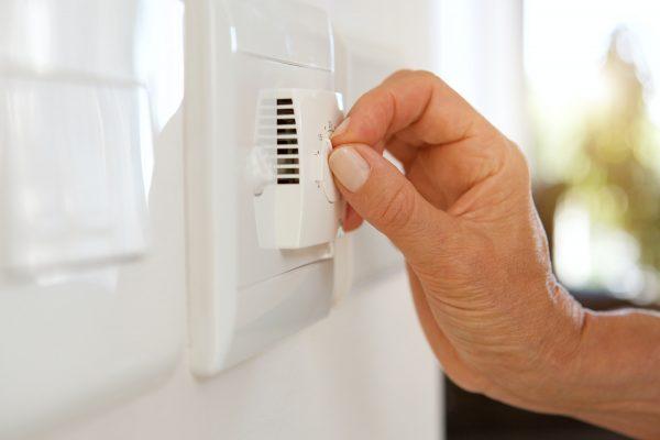female hand adjusting temperature with dial on air conditioning